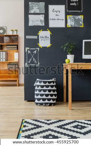 Cropped shot of a large blackboard wall with posters in a modern living room - stock photo