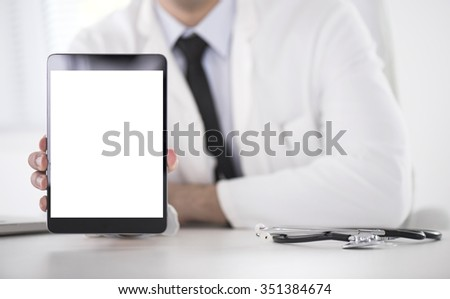 Cropped shot of a male doctor using a digital tablet.He is showing digital tablet with blank screen to the camera.Selective focus on digital tablet - stock photo