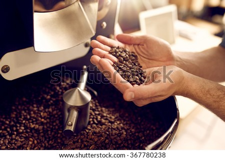 Cropped shot of a man's hands holding freshly roastd aromatic coffee beans over a modern machine used for roasting beans - stock photo