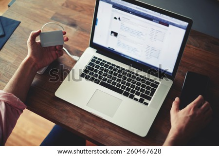 Cropped shot of a man's hands using a laptop at home while holding credit card, data security, on-line shopping at home, cross process, filtered image, focused on the left hand with gift card - stock photo