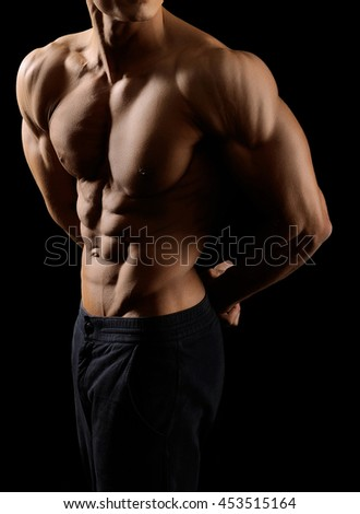 Cropped shot of a ripped man body on black background - stock photo
