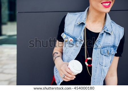 Cropped shot of a trendy stylish woman's hands holding a coffee to go. Urban girl with her style - stock photo
