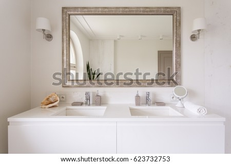cropped shot of a white vanity top with two sinks and a stylish mirror in bathroom