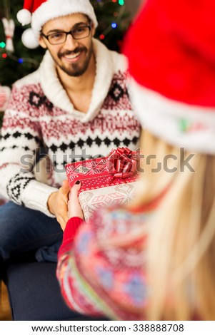 Cropped shot of a woman surprising her boyfriend with a Christmas gift. Selective focus in the middle of the frame. - stock photo
