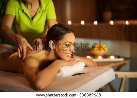 Cropped shot of an attractive young woman enjoying a relaxing massage at the spa. Ambiental light, selective focus on the closer eye. - stock photo