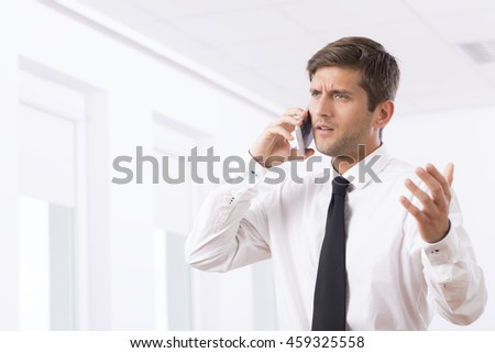 Cropped shot of an unhappy employee arguing with someone on the phone - stock photo