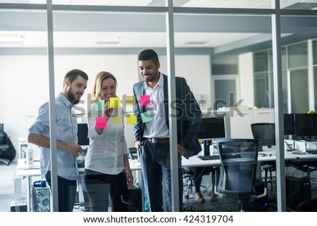 Cropped shot of coworkers using sticky notes on a glass wall during a meeting.