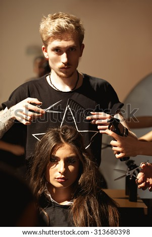 Cropped shot of fashion stylist-hairdresser and attractive young woman client model in the hair beauty salon. Stylist holding scissors and comb over the head of the client is preparing to do her hair. - stock photo