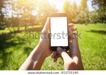 Cropped shot of female hands holding cell phone with blank copy space screen for your text or information content. Woman using mobile phone while walking in the park, Selective focus, film effect  - stock photo