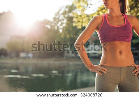 Cropped shot of fit young woman in sportswear standing with her hands on hips outdoors. Female runner ready for a run with sun flare. - stock photo