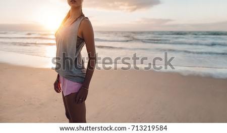 Cropped shot of fitness woman standing on the beach. Sporty female on the sea shore in morning for workout.