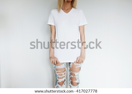 Cropped shot of hipster model wearing blank white T-shirt with copy space for your advertising content. Young Caucasian teenage girl posing indoor against home interior background. Lifestyle concept  - stock photo