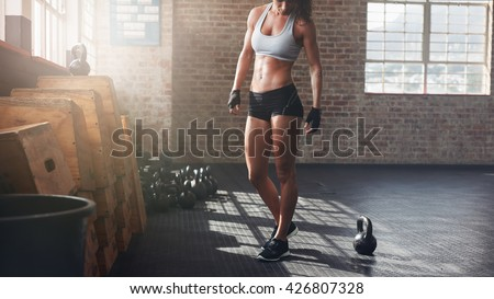 Cropped shot of muscular woman standing in gym. Fitness female model in sportswear with kettle bell on floor. - stock photo
