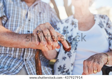 Cropped shot of senior couple holding hands while sitting together. Focus on hands on walking stick. - stock photo