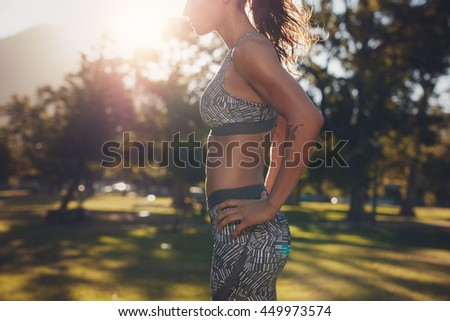 Cropped shot of strong young woman standing with her hands on hips. Strong woman with sixpack abdominals. Fit female athlete in sportswear standing at a park. - stock photo