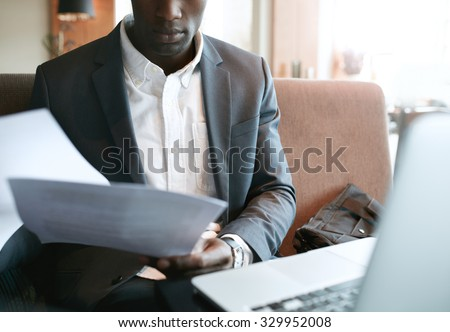 Cropped shot of young businessman going through some paperwork. African business executive reading documents while sitting at coffee shop. - stock photo