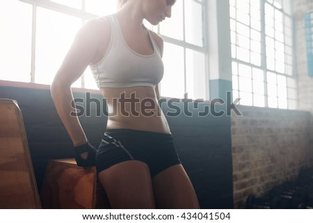 Cropped shot of young woman body with muscular abs standing in the gym. Healthy female model in sportswear relaxing after her workout. - stock photo