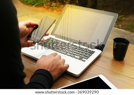 Cropped shot Silhouette of a man's hands using a laptop at home, rear view, young male student typing on computer sitting at wooden table, phone on table, coffee, filter sun - stock photo