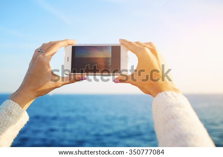 Cropped shot view of a woman's hands holding cell telephone to make photo with  digital camera of sunset, female photographing sea landscape on smart phone during walking on quay in summer evening - stock photo