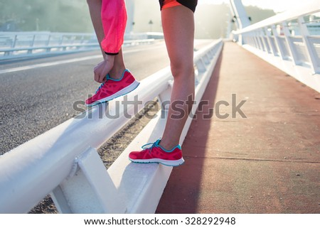 Cropped shot view of female jogger tying laces on her colorful running shoes while relaxing after fit training outside, young athletic woman tie shoelaces while taking break between workout outdoors - stock photo