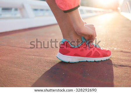 Cropped shot view of fit woman tie shoelaces while standing on asphalt road during jog in summer evening, athletic female tying the laces on running shoes while taking break between training outside  - stock photo
