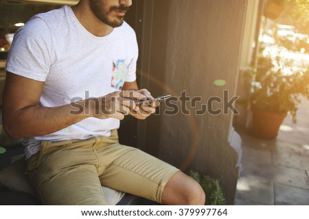 Cropped shot view of hipster guy reading text message on cell telephone while sitting outdoors in summer season, young bearded man dressed in casual clothes using mobile phone during recreation time - stock photo