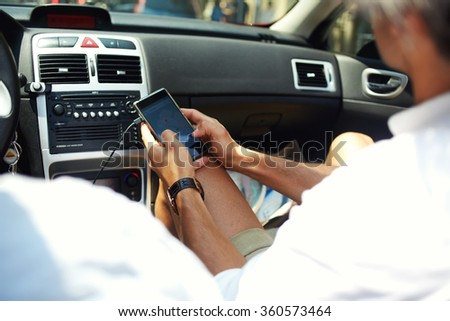 Cropped shot view of man checking location map on cell telephone while sitting near the driver, male passenger using mobile smart phone for navigation application with planned route on the screen - stock photo