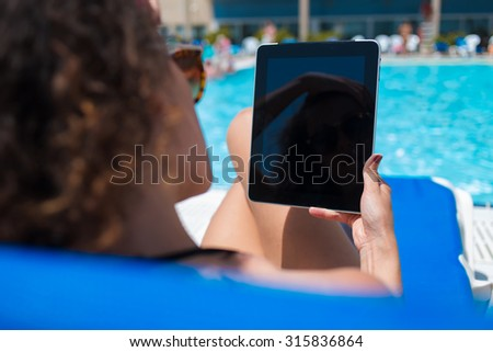 Cropped shot view of woman reading book on touch pad while relaxing near pool during summer vacation,young female in bikini holding digital tablet with blank copy space screen for your content or text - stock photo