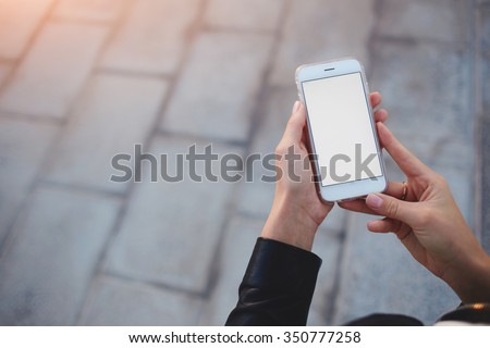 Cropped shot view of woman's hands holding smart phone with blank copy space screen for your text message or information content, female reading text message on cell telephone during in urban setting - stock photo