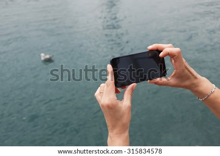 Cropped shot view of woman's hands holding smart phone with copy space area for your text message or advertising content, female photographing sea view with cell telephone camera during summer trip - stock photo