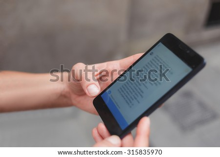Cropped shot view of woman's hands holding smart phone with copy space area for your text message or advertising content, female chatting on her cell telephone while strolling on the street  - stock photo