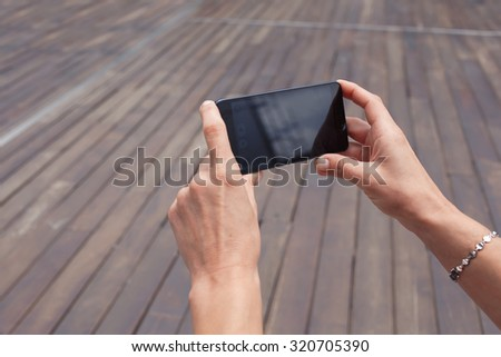 Cropped shot view of woman's hands holding smart phone with copy space area for your text message or advertising content, hipster girl photographing on mobile phone for social network picture  - stock photo