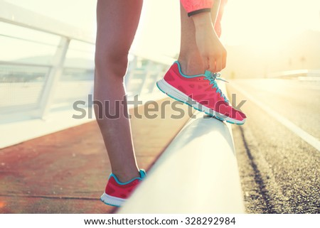 Cropped shot view of woman's hands tie shoelaces while standing on road for jogging against sunset, young athletic female tying the laces on her running shoes while taking break during intense workout - stock photo