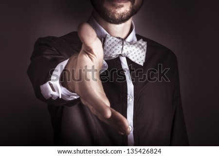 Cropped torso portrait of a polite fashionable sophisticated man wearing a dinner jacket and bow tie offering his hand in an act of chivalry or greeting