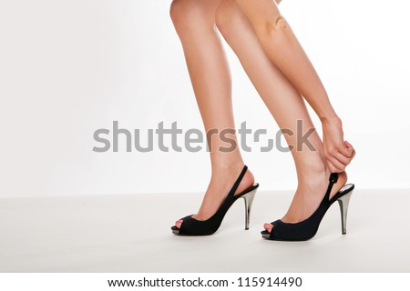 Cropped view image of a beautiful shapely pair of female legs wearing high heels with the woman stooping to adjust her shoe - stock photo