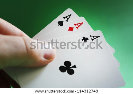 Cropped view image of a male hand playing poker holding three aces over a green background - stock photo