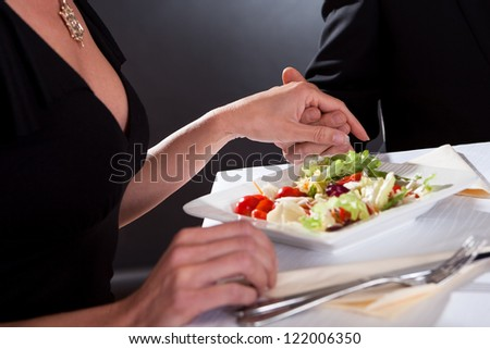 Cropped view image of a man and woman holding hands while enjoying a romantic dinner - stock photo