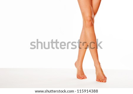 Cropped view image of a pair of beautiful tanned female legs walking elegantly on tip toe over white with copyspace