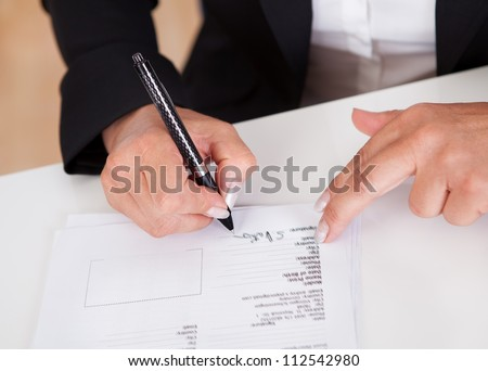 Cropped view image of female hands signing a document with a ballpoint pen