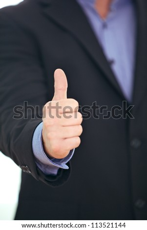 Cropped view image of the hand of a businessman giving a thumbs up gesture of approval , acceptance and success