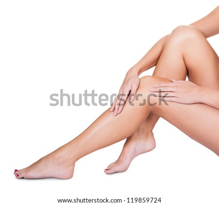 Cropped view image of the hands of woman sitting caressing her bare silky smooth sexy legs isolated on white - stock photo