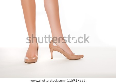 Cropped view image of the shapely legs of a woman in stylish simple high heeled shoes on a white background