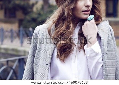 Cropped view of a girl in the city wearing a coat with white shirt and brown curly long hair