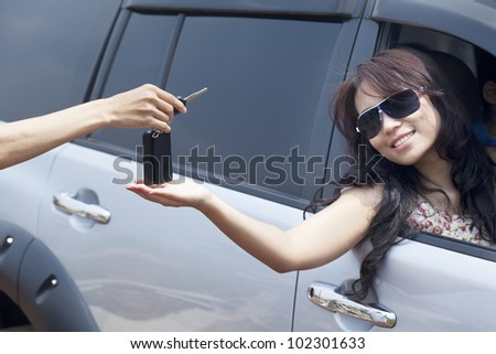 Cropped view of a hand giving a car key to beautiful asian woman
