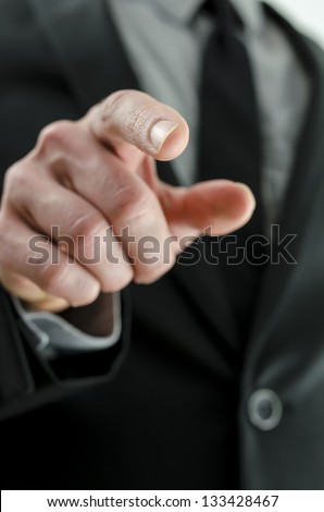 Cropped view of a hand with pointed finger. With businessman in suit in background.