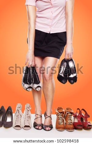 Cropped view of a woman with a passion for shoes and shapely legs wearing sandals standing in a line of shoes while also holding two pairs - stock photo