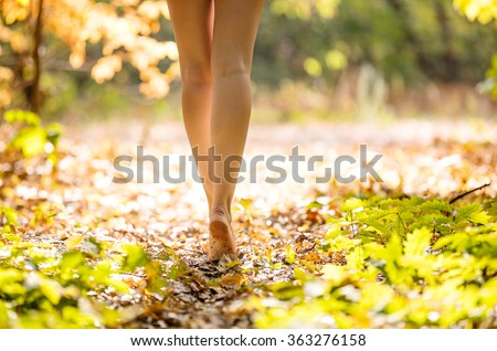 Cropped view of beautiful young woman walking in forest barefoot - stock photo