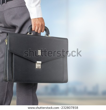 Cropped view of businessman holding a briefcase in the office