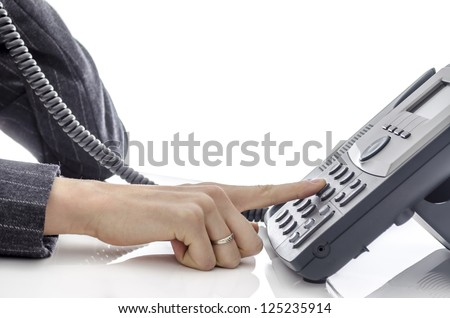 Cropped view of female hand dialing a phone number. - stock photo