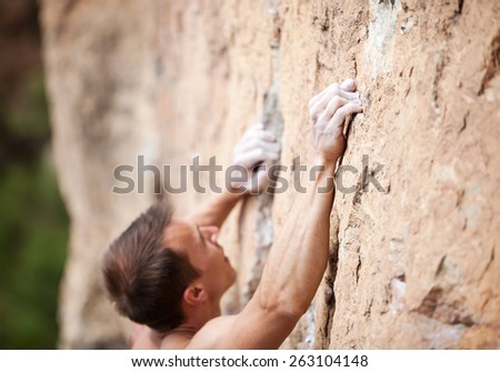 Cropped view of male rock climber on cliff, hands in focus - stock photo